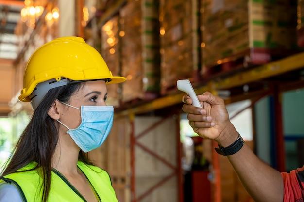 Lagerarbeiter, körpertemperaturprüfung, virusprävention konzepte zur vorbeugung ansteckender krankheiten, körper für medizinische infrarot-thermometer verwenden. Premium Fotos