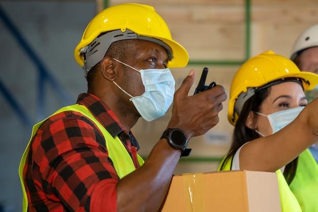 Lagerarbeiter mit schutzmaske arbeiten im lager. sie arbeiten in der industriefabrik. Premium Fotos