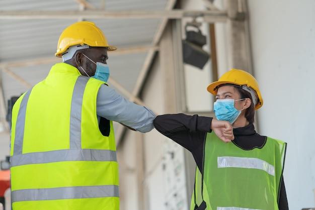 Lagerarbeiter tragen eine gesichtsmaske zum schutz des coronavirus und begrüßen die ellbogen in der logistiklagerfabrik Premium Fotos