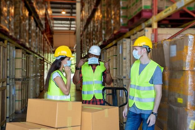 Lagerarbeiter tragen eine schutzmaske zum schutz vor covid-19 mit zwischenablage während der arbeit in einem lager. Premium Fotos