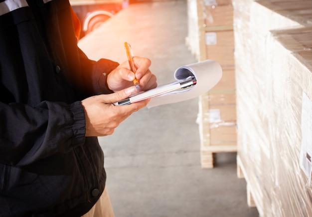 Lagermitarbeiter halten eine zwischenablage mit inventar der sendungspalette. Premium Fotos