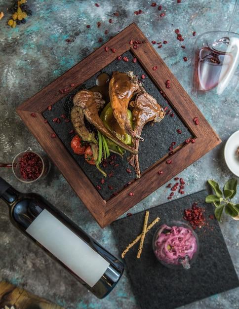 Lammknochenkebab mit einer flasche rotwein Kostenlose Fotos