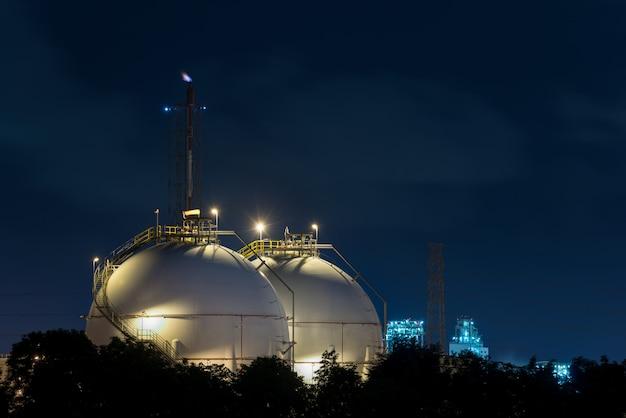 Landschaft der erdölraffinerieindustrie mit ölvorratsbehälter in der nacht. Premium Fotos