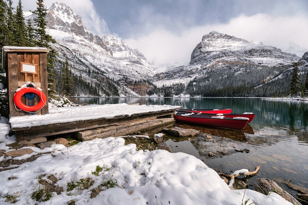 Landschaft des lake o'hara mit rotem kanu im hölzernen dock am winter im yoho-nationalpark Premium Fotos