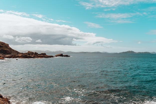 Landschaft des meeres umgeben von einer insel im grünen unter einem bewölkten himmel bedeckt Kostenlose Fotos