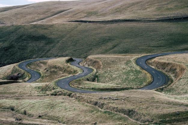 Landschaft einer kurvigen straße, umgeben von hügeln, die tagsüber mit gras bedeckt sind Kostenlose Fotos