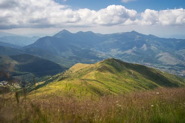 Landschaft von hügeln bedeckt im grünen mit felsigen bergen unter einem bewölkten himmel auf dem Kostenlose Fotos