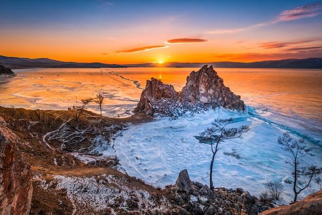 Landschaft von shamanka-felsen bei sonnenuntergang mit natürlichem brechendem eis in gefrorenem wasser auf dem baikalsee, sibirien, russland. Premium Fotos