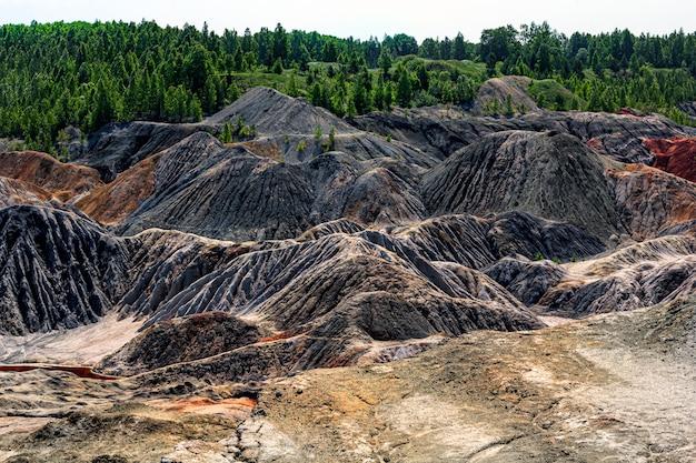 Landschaft wie eine marsoberfläche des planeten. erstarrte rotbraune schwarze erdoberfläche. gebrochenes und verbranntes land. feuerfeste tonsteinbrüche. Premium Fotos