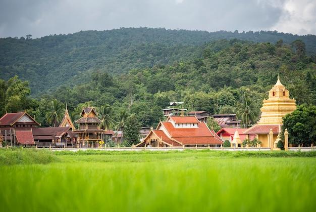 Landschaftsansicht des grünen reisfeldes mit altem tempel in goldener pagode und im berg thailands Premium Fotos