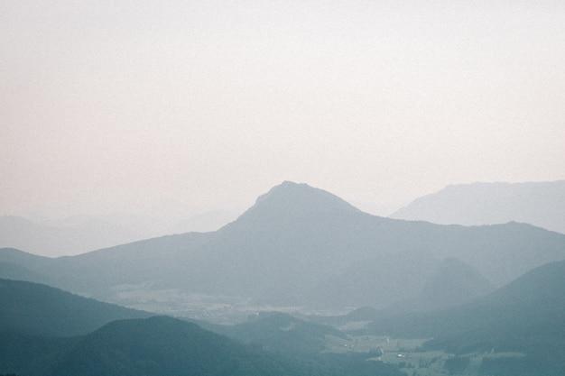 Landschaftsaufnahme eines nebligen berges mit einem düsteren himmel im hintergrund Kostenlose Fotos