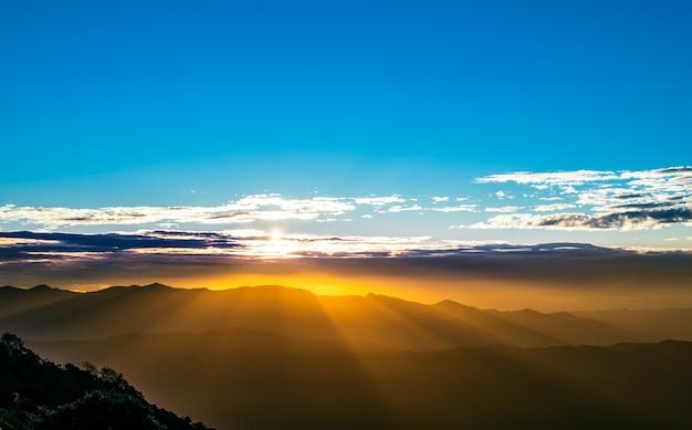 Landschaftsbilder der morgensonne, wo ein schöner lichtstrahl die bergkette bedeckt, und das licht, das auf den wolken am himmel reflektiert wird, zum naturhintergrundkonzept. Premium Fotos