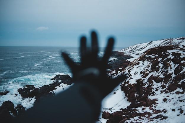 Landschaftsfotografie der klippe bedeckt mit schnee, das gewässer betrachtet Kostenlose Fotos