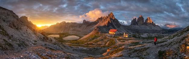 Landschaftspanoramaansicht des hauses und des berges mit goldhimmel auf sonnenuntergang von tre cime, dolomit, italien. Premium Fotos
