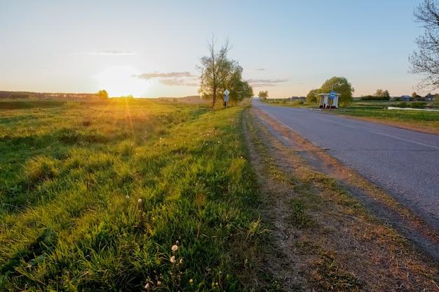 Landstraße im dorf nahe bei dem feld bei sonnenuntergang Premium Fotos
