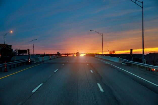 Landstraße mit bewölktem himmel angesichts des dämmerungssonnenuntergangs Premium Fotos