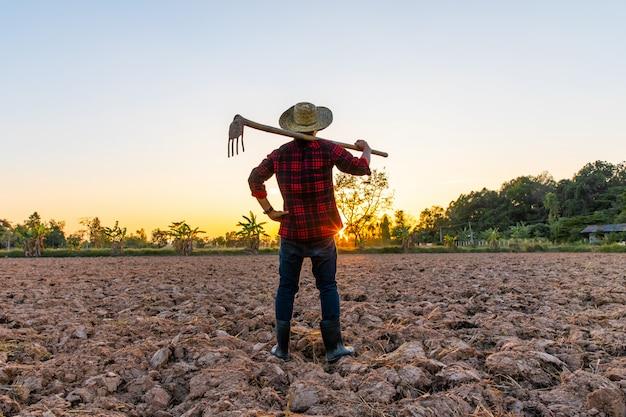 Landwirt, der an feld bei dem sonnenuntergang im freien arbeitet Premium Fotos