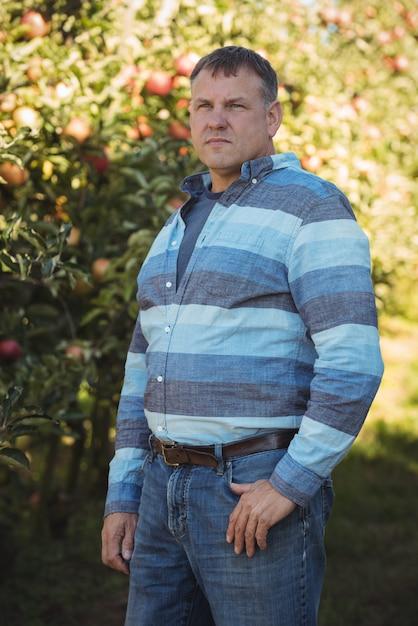 Landwirt, der im apfelgarten steht Kostenlose Fotos