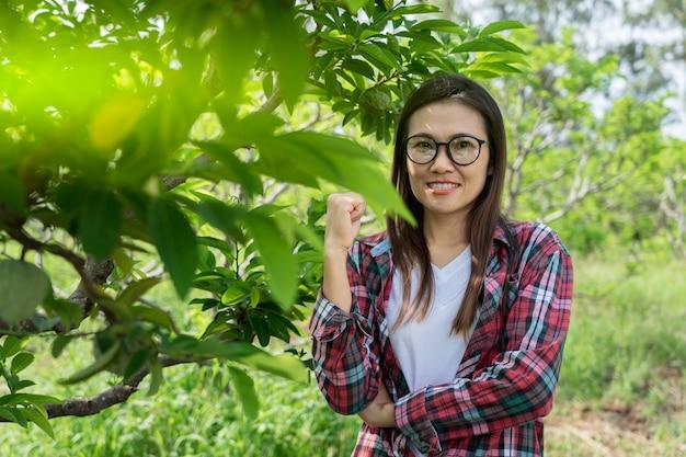 Landwirt des jungen mannes, der im vanillepuddingapfelbaumobstgarten lächelt und steht. Premium Fotos