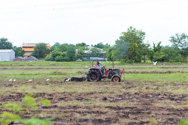 Landwirt im traktor, der land mit saatbeetlandwirt vorbereitet Premium Fotos