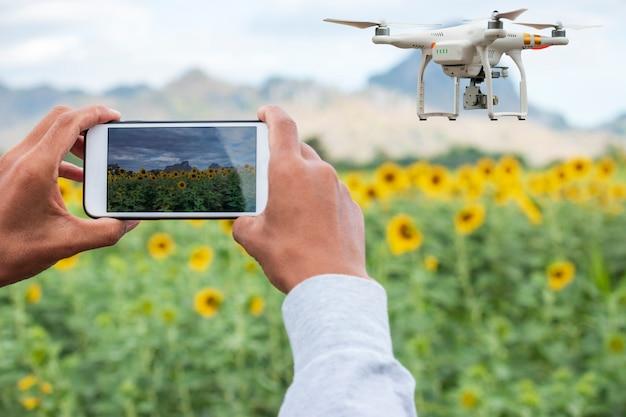 Landwirt mit intelligentem telefon auf feld mit dem brummen, das über ackerland fliegt Premium Fotos