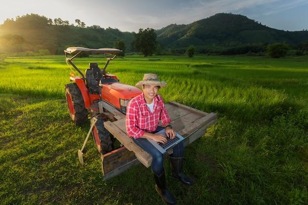 Landwirt verzeichnete wachstum der produktivität, die auf einem traktor im hintergrund ein reispaddy sitzt Premium Fotos