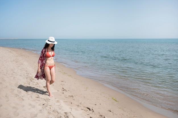 Lang von der frau, die am strand geht Kostenlose Fotos