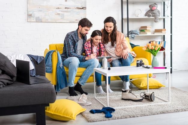 Lange aufnahme von glücklicher familie und unordentlichem zuhause Kostenlose Fotos