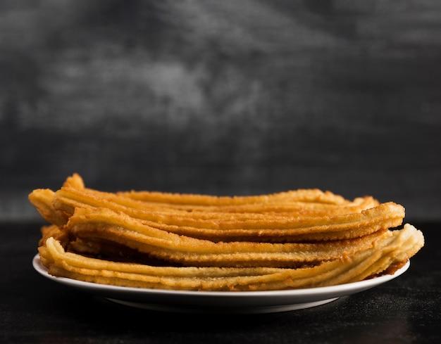 Lange sicht der weißen platte mit churros gefüllt Kostenlose Fotos
