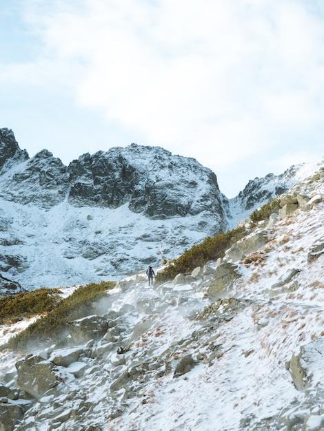 Lange vertikale aufnahme einer winterlandschaft mit einem mann, der an den tatra-bergen in polen wandert Kostenlose Fotos