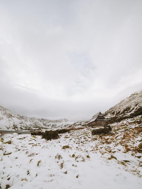 Lange vertikale aufnahme einer winterlandschaft mit einer kleinen hütte an den tatra-bergen in polen Kostenlose Fotos