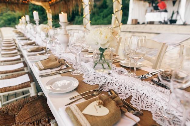 Lange weiße tisch steht unter weißen zelten am sandstrand Kostenlose Fotos
