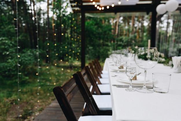 Langer tisch für gäste, die für eine schöne hochzeit im freien in einem zelt oder pavillon eingerichtet sind Premium Fotos
