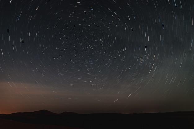 Langes belichtungsfoto des himmels in der sahara-wüste, sternspuren nachts schauend. Premium Fotos