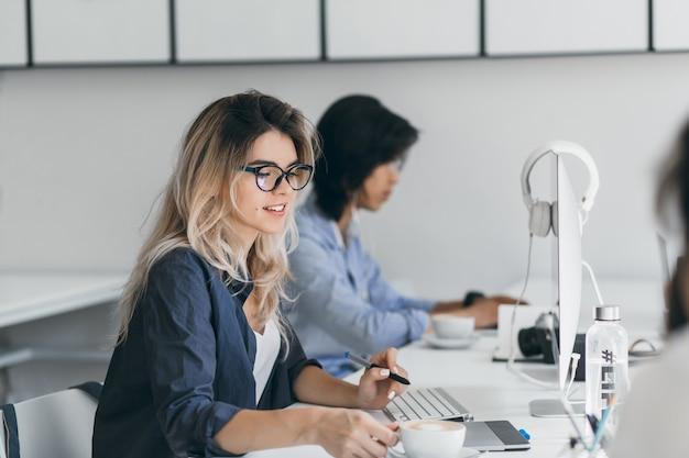 Langhaarige programmiererin, die eine tasse kaffee hält, die sich von der arbeit entspannt. innenporträt des europäischen it-spezialisten, der am arbeitsplatz mit lächeln neben asiatischem jungen mann sitzt. Kostenlose Fotos