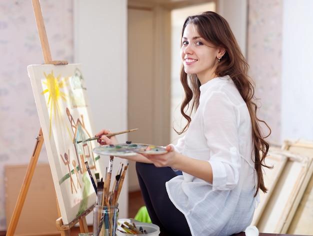 Langhaariger Weiblicher Künstler Malt Bild Auf Segeltuch Download