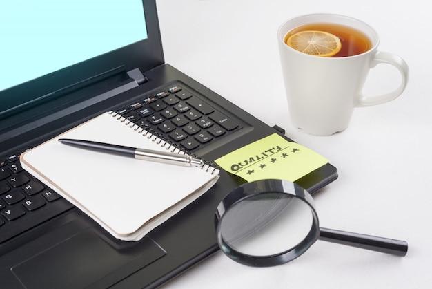 Laptop auf dem schreibtisch, aufkleber mit wortqualität Premium Fotos