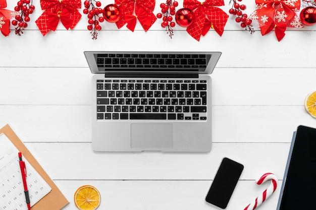 Laptop auf dem weißen hölzernen schreibtisch umgeben mit roten weihnachtsdekorationen Premium Fotos