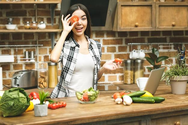 Laptop auf küchentisch und kochendes schönes lächelndes mädchen. entspannen Premium Fotos