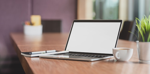 Laptop-computer des leeren bildschirms und ein tasse kaffee im modernen konferenzzimmer Premium Fotos
