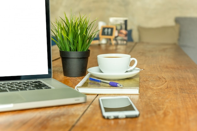Laptop-computer mit kaffeetasse und handy auf holztisch im café. Premium Fotos
