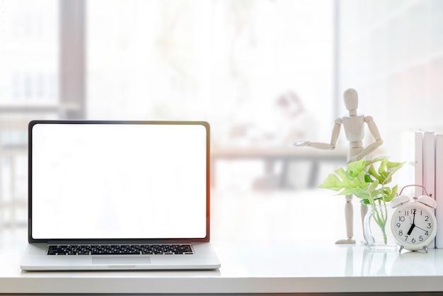 Laptop des leeren bildschirms des modells auf weißer hölzerner tabelle im mitarbeitenden raum. Premium Fotos