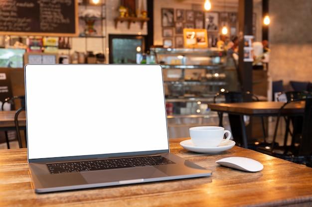 Laptop des leeren bildschirms mit maus und kaffeetasse auf holztisch in coffe shop. Premium Fotos