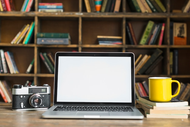 Laptop des leeren bildschirms mit retro- kamera; gelbe kaffeetasse; buch auf tisch im bibliotheksraum gestapelt Kostenlose Fotos