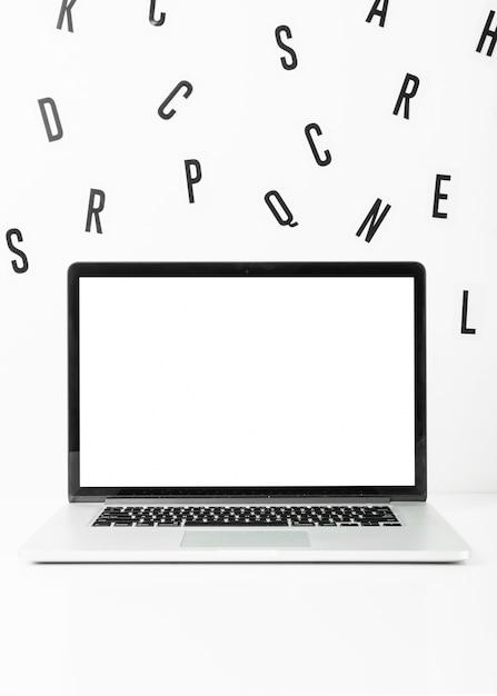 Laptop des leeren bildschirms mit zerstreuten alphabeten auf weißem hintergrund Kostenlose Fotos