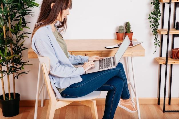 Laptop des Mädchens sufring bei Tisch Kostenlose Fotos
