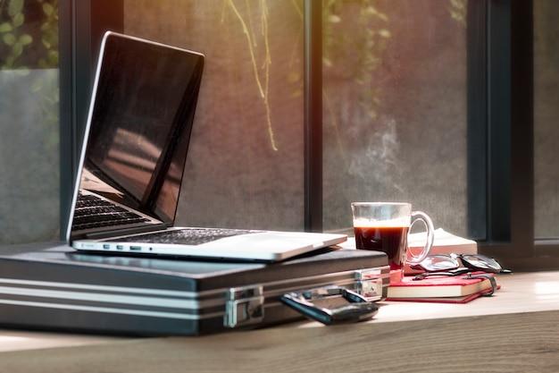 Laptop, dokumententasche, brille und buch im café öffnen. Premium Fotos