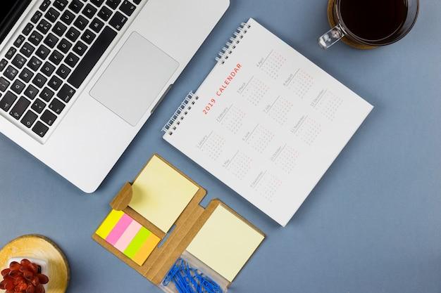 Laptop in der nähe von kalender, aufkleber und tasse getränk Kostenlose Fotos