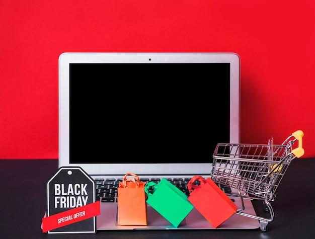 Laptop in der nähe von spielzeug-pakete, zeichen und einkaufswagen Kostenlose Fotos