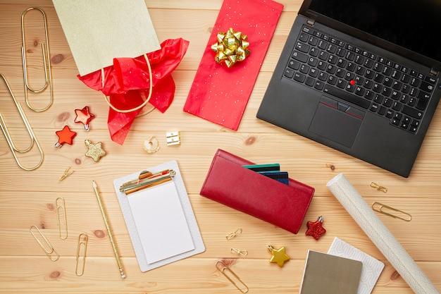 Laptop, kreditkarten, geldbeutel und weihnachtsdekoration. online weihnachtseinkäufe, geschenke kaufen Premium Fotos